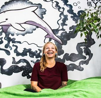 Gina Falcetta Smiling in Front of Howard the Dolphin